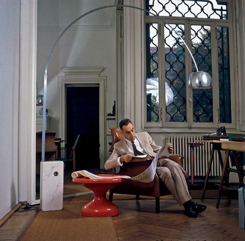 """Achille Castiglioni ien su estudio bajo su lámpara arco """"Arco"""" (1962), sentado en su silla""""Sanluca"""" al lado de su mesa""""Rochcetto""""."""